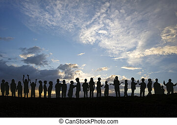 Silhouette of long line of children messing around against...