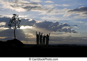 Silhouette of four young children against stunning sunset with s