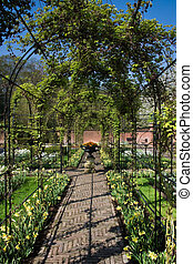Springtime in formal garden with pergola and vase ornament