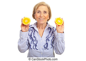 Healhty senior woman holding orange - Healthy senior smiling...
