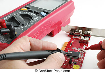 Multimeter and circuit board - Computer technician examining...