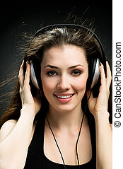 girl in headphones on the black background