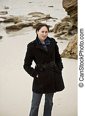 Attractive caucasian woman in warm clothing on beach,...
