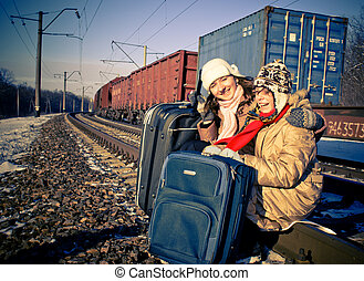 Two laughing sisters sitting at the railroad with suitcases