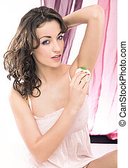 Young beautiful brunette shaving her armpit
