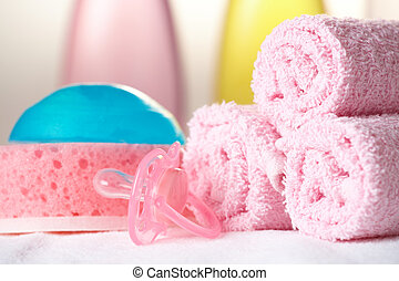 Baby care objects. Olive, shampoo in background towels,...