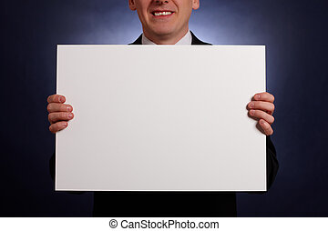 Smiling businessman holding a big blank card