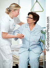 nursing - Nurse helps a patient to get up in hospital