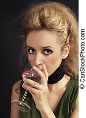 young woman with stylish hair drinking white wine from the...