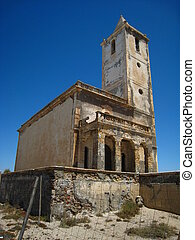 Old abandoned white church with bell tower, almost in ruins