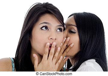 woman telling her friend a secret