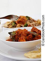 Rendang chicken - A fork picks a piece of Rendang chicken