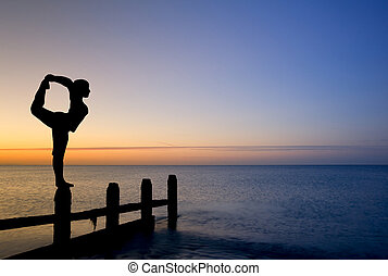 Silhouette of woman stretching doing yoga on groynes on...