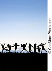 Silhouette of group of children jumping in the air against...