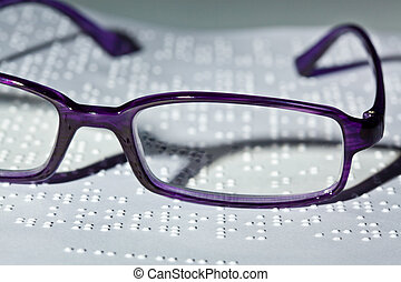 Glasses and book in Braille. - A pair of glasses and a book...