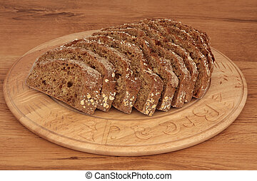 Soda Bread - Soda bread loaf in slices on a carved wooden...