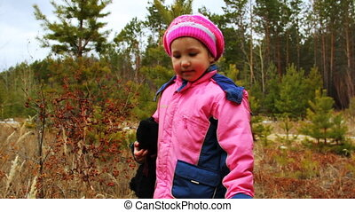 Little girl walking and playing outdoor in the autumn forest