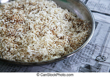 Grated - ToastedBaked dessicated coconut in a plate on...