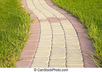 Brick Sidewalk - Garden stone path with grass growing up...