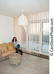 Woman relaxing in a modern room - Beautiful woman sitting on...