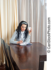 Business woman working late sitting at meeting table with a...
