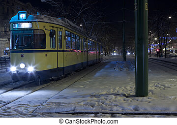 yellow tram in a cold winter night with snow and ice on it