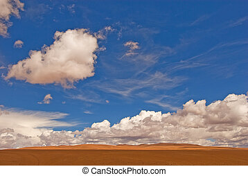 desert landscape white clouds and deep blue sky