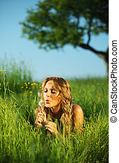 i wish -  woman blow on dandelion on green field under tree