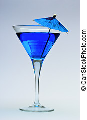 Blue cocktail inside glass and paper decorative parasol