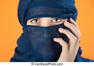 Blue scarf covered woman - Young woman covers her face with...