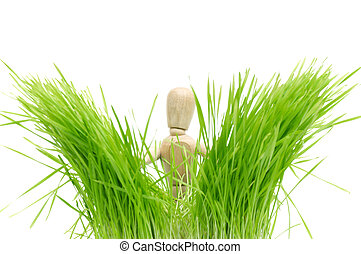 A wooden mannequin on green grass isolated