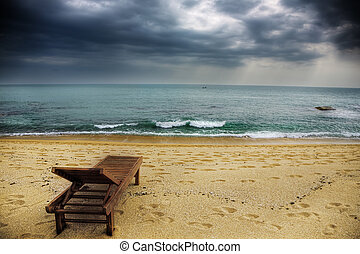 stormy beach - a lonely lounger on the stormy beach
