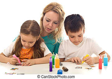 Kids busy painting with lots of colors, supervised by their...