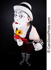 Funny mime in white hat with a bouquet of flowers