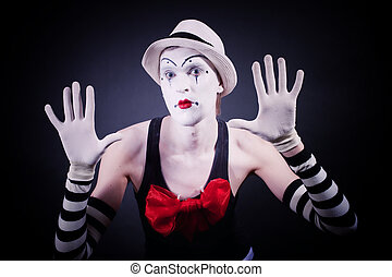 Mime with red bow in a white hat and striped gloves on black...