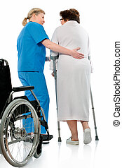 in hospital - nurse helps a senior woman on crutches in...
