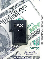 Tax return - Computer enter key on top of a pile of...