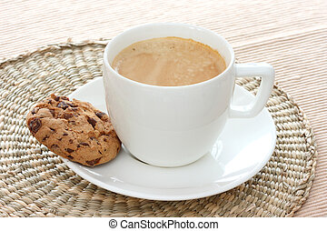 Chocolate chip cookie on saucer with coffee - Close up view...