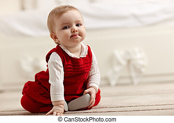 little girl sitting on carpet, looking at camera - portrait...