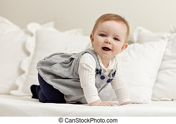 little girl walking all fours on bed - portrait of 6 months...
