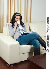 Woman on sofa drinking coffee and reading - Woman sitting on...