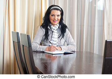 Happy woman writing at table - Happy smiling business woman...