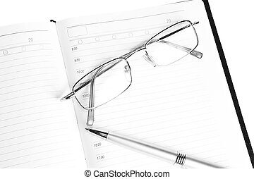 pen notebook and glasses in composition in black and white