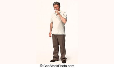 Retired man drinking medicine against a white background