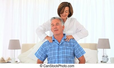 Mature woman giving her husband a massage in the bedroom