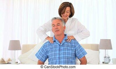 Mature woman giving her husband a massage