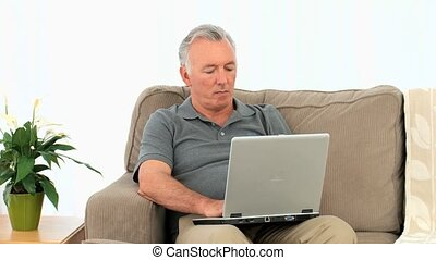 Senior man working on his laptop on his armchair