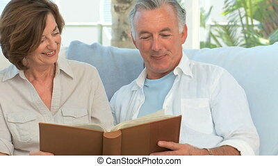 Mature couple looking at a photo album in the living room
