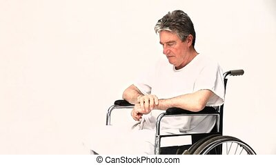Man in a wheelchair waiting for his nurse against a white...