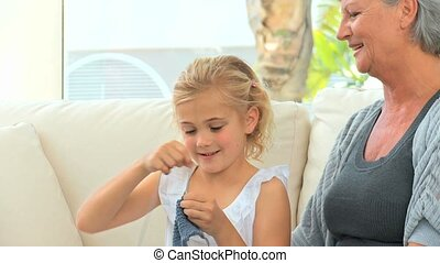 Grandmother teaching her grand daughter how to knit on a...
